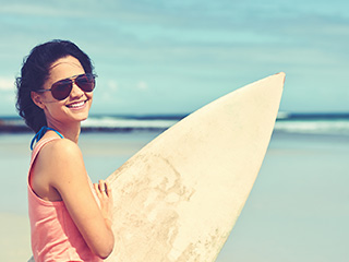 woman in sunglasses holding surf board